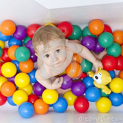 Cute baby boy playing with colorful plasic balls in the bathtub