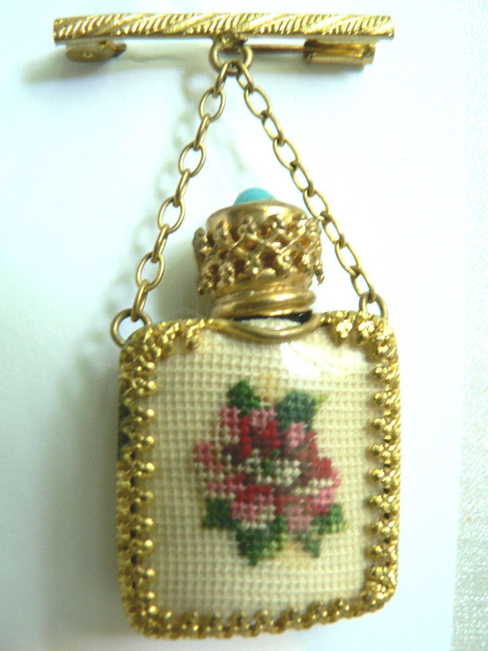 this beautiful brooch has a dangling perfume bottle with a lovely petit point hand crafted