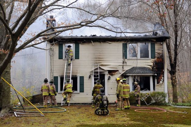 Firefighters work at 409 Frogtown Road in New Canaan where a two-story home was a total loss after a fire just after noon on Wednesday, April 11, 2012. Photo: Lindsay Niegelberg / Stamford Advocate