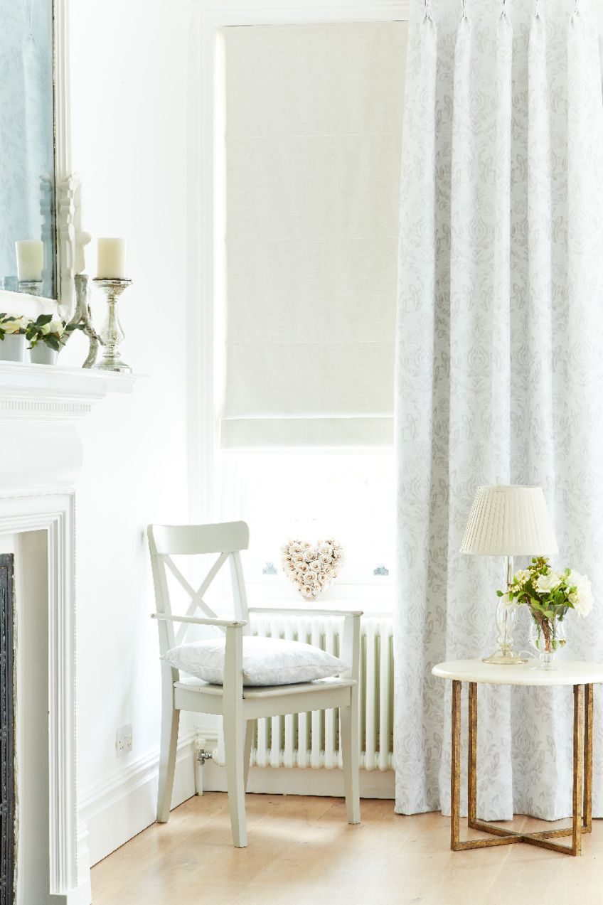 white Roman blinds and curtains in this living