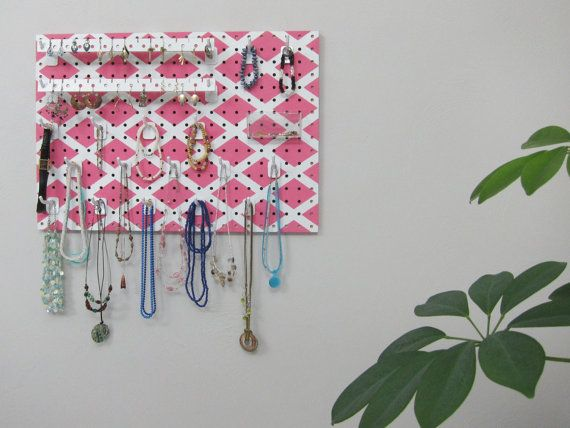 This colorful pink jewelry organizer hangs on your wall or closet door.  Each long hook holds multiple necklaces, bracelets, rings, and more.  It also has special earring holders and even a clear basket for pins and brooches.   No more tangled necklaces buried in a box!  Wall Hanging Jewelry Organizer  by JansJewelryOrganizer, $47.95