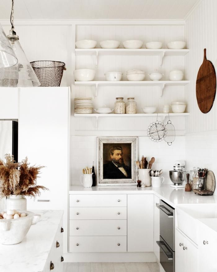 Inspired by old, hard-working kitchens (i.e. bakeries or butcher shops), Kara selected materials that were durable and practical for food preparation. Salvaged elements, including the open shelving, as well as traditional fixtures (marble countertops and a butler's sink), create an updated old-world feel.