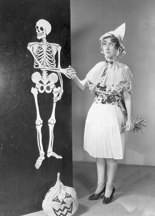 A Costumed Woman Shakes Hands With Life Sized Halloween Skeleton Decoration Hanging On Wall