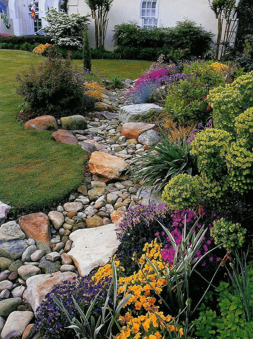 A dry creek bed design in the home landscape creates interest and provides