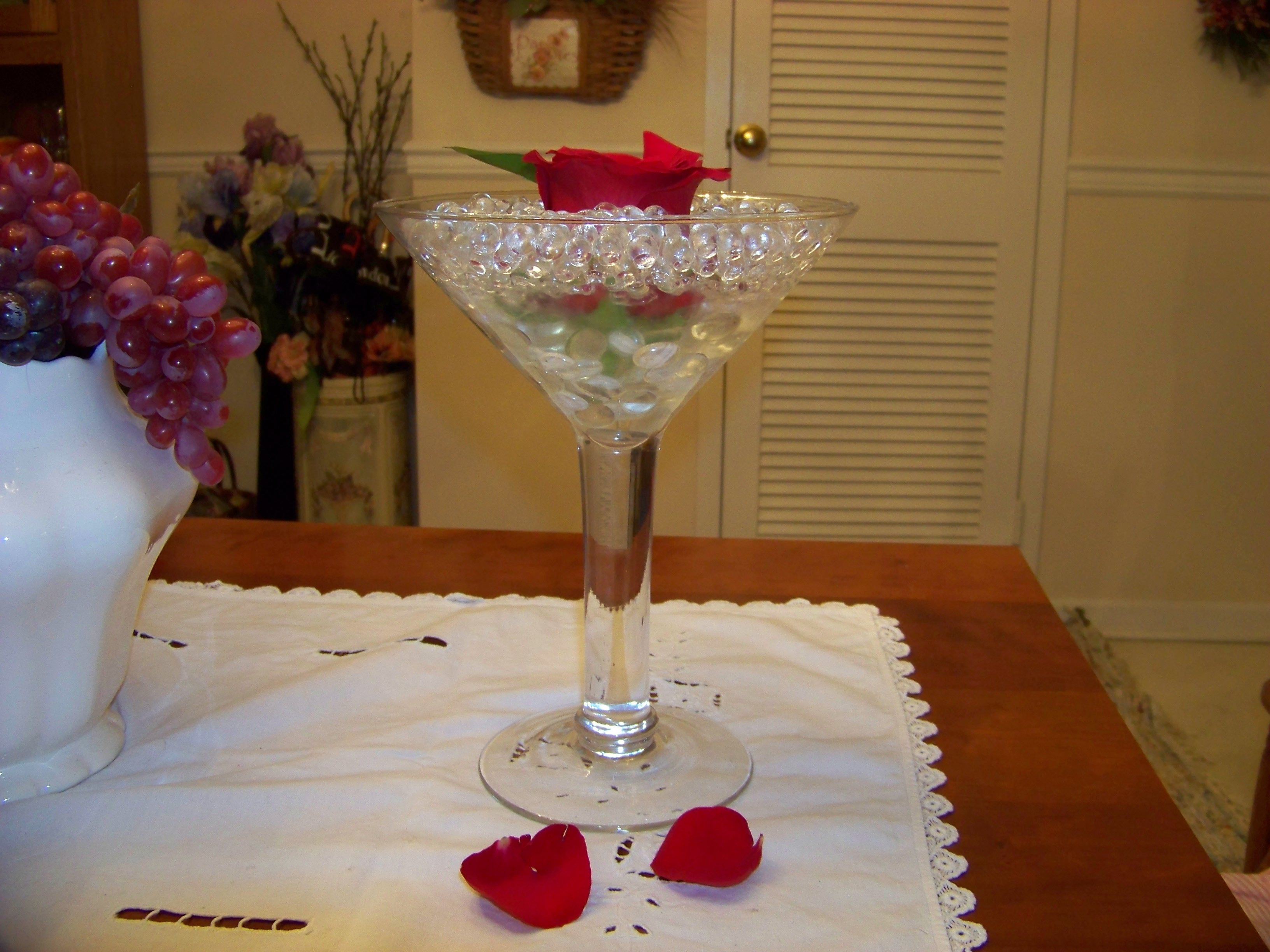 Martini glass filled with crystals and open rose
