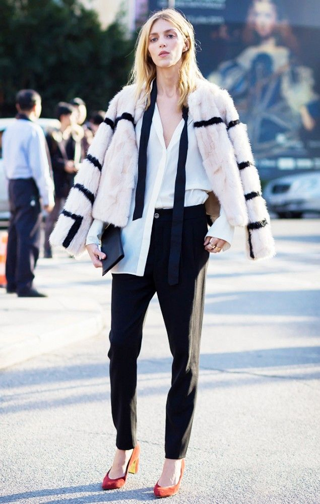 Anja Rubik wears a sheer button-down blouse, striped fur coat, black trousers, and suede heels