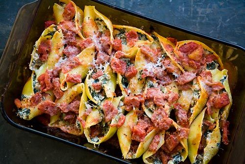 Jumbo pasta shells stuffed with Italian sausage, spinach, ricotta and Parmesan cheeses, covered with cooked tomatoes and baked.