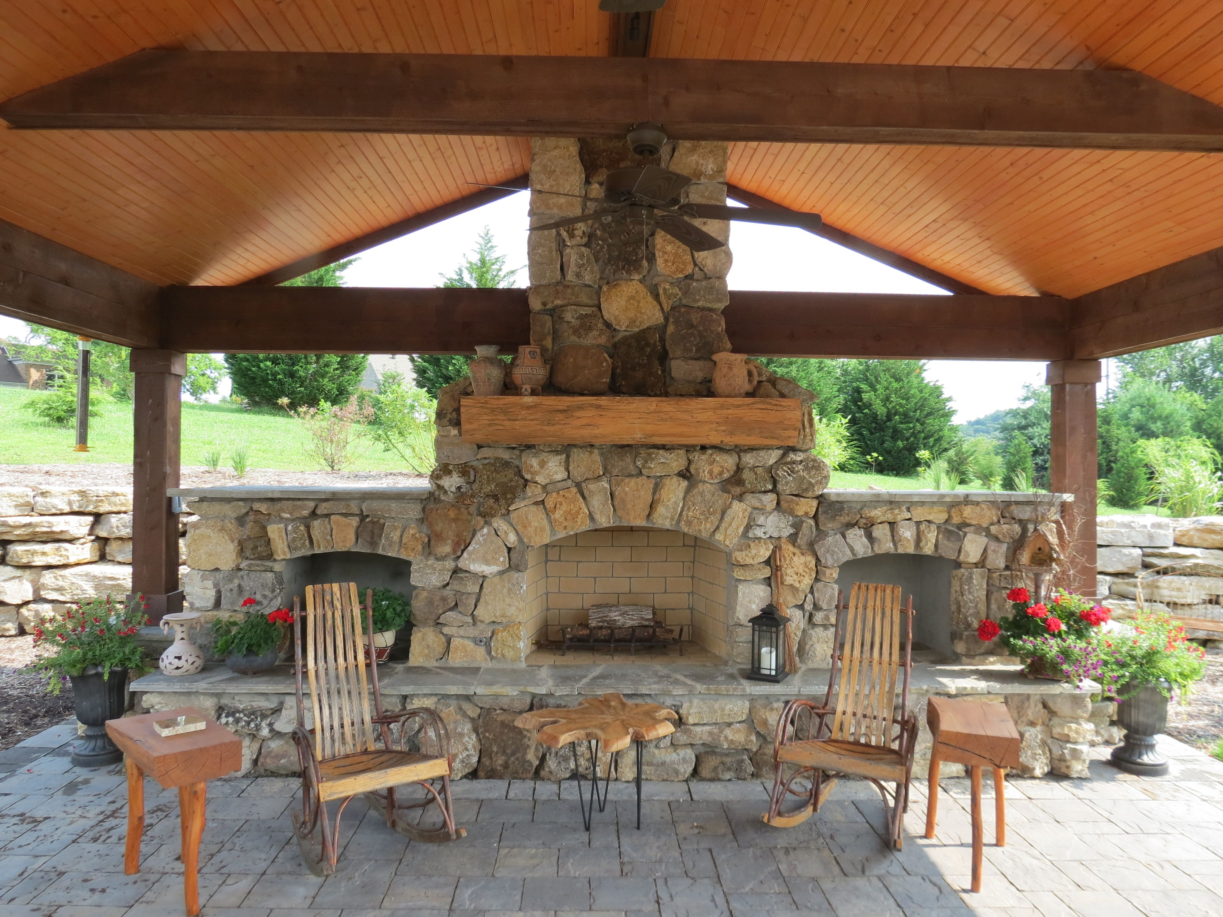 Natural stone fireplace with wood storage and brick paver patio ...