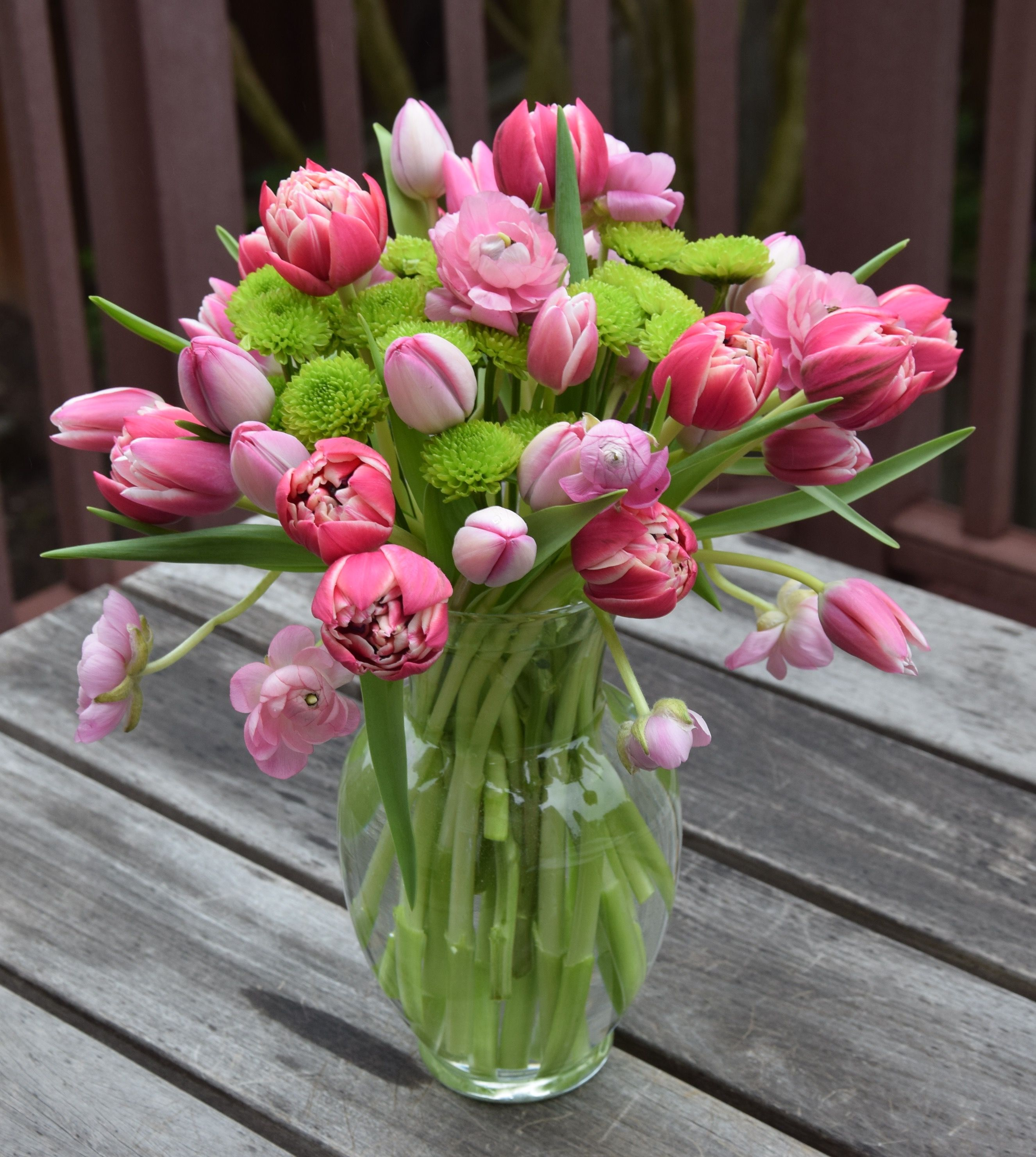 A bouquet of tulips and ranunculus and pom poms fresh