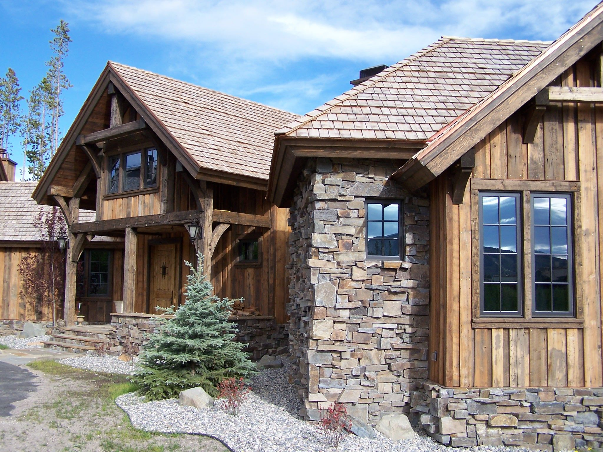 Like the vertical siding rustic feel bavarian stone for Alpine home designs