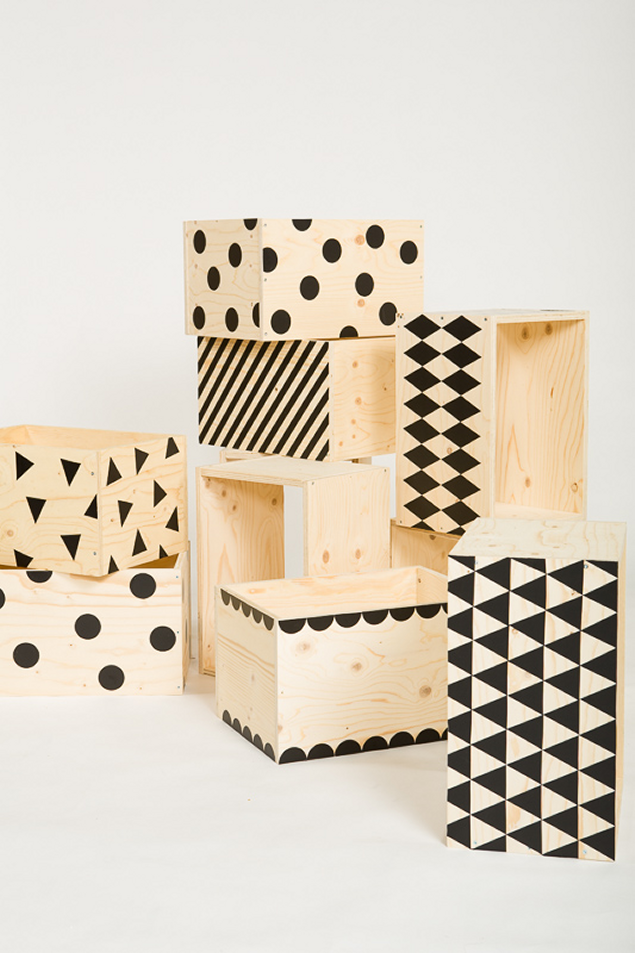 Geometric patterns painted on wooden storage crates--I bet you could use wall decals to make the design too if you sealed the wood first.