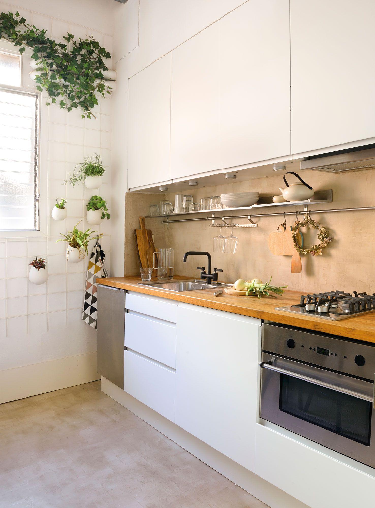 Cocina con muebles en blanco, encimera de madera y suelo de ...