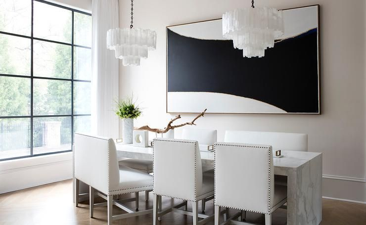 Sleek Modern Black And White Dining Room Boasts Two White Tiered Capiz Chandeliers Hun Luxury Dinning Room Upholstered Dining Bench Black And White Dining Room