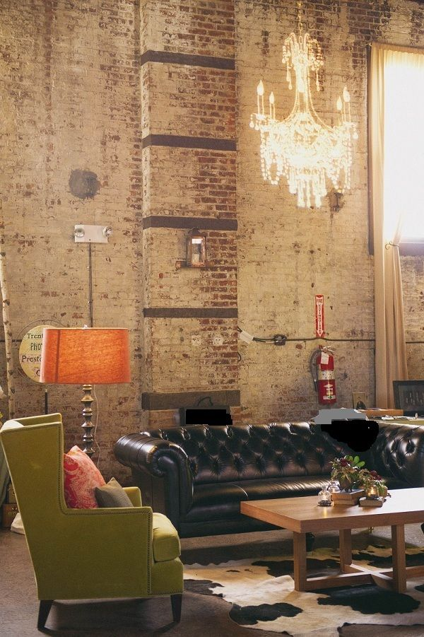 looking at colour, the orange lamp and green chair against the dark leather sofa.