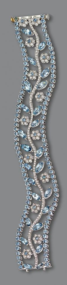 AQUAMARINE AND DIAMOND BRACELET. The openwork serpentine band decorated with a central branch supporting flowers and leaves, set with marquise-shaped and round aquamarines as well as numerous small round diamonds, mounted in platinum, length 7¼ inches. Pinned from sothebys.com
