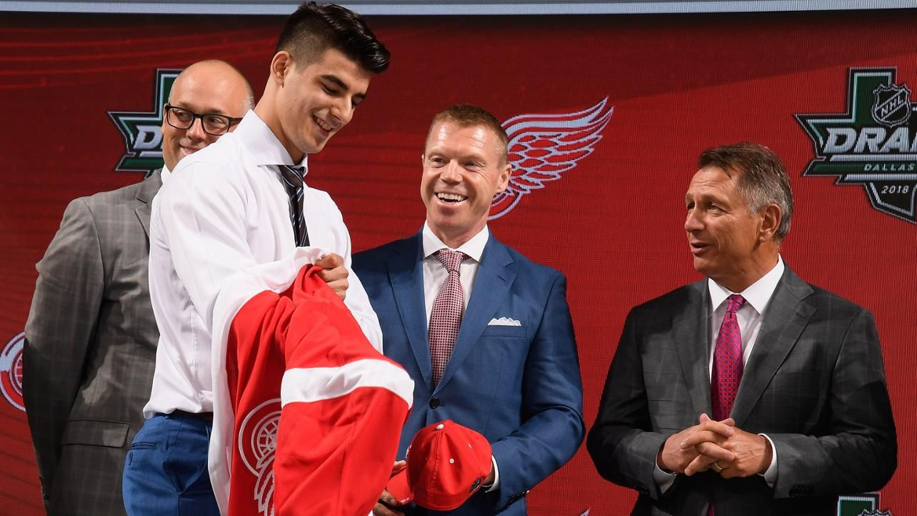 Center Joseph Veleno puts on a Detroit Red Wings jersey as coach Jeff  Blashill c03e738b6