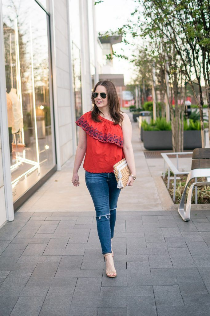 ab8c637bdd96b7 Fashion blogger shows houston street style in a spring outfit idea  featuring a red one shoulder top with distressed jeans.