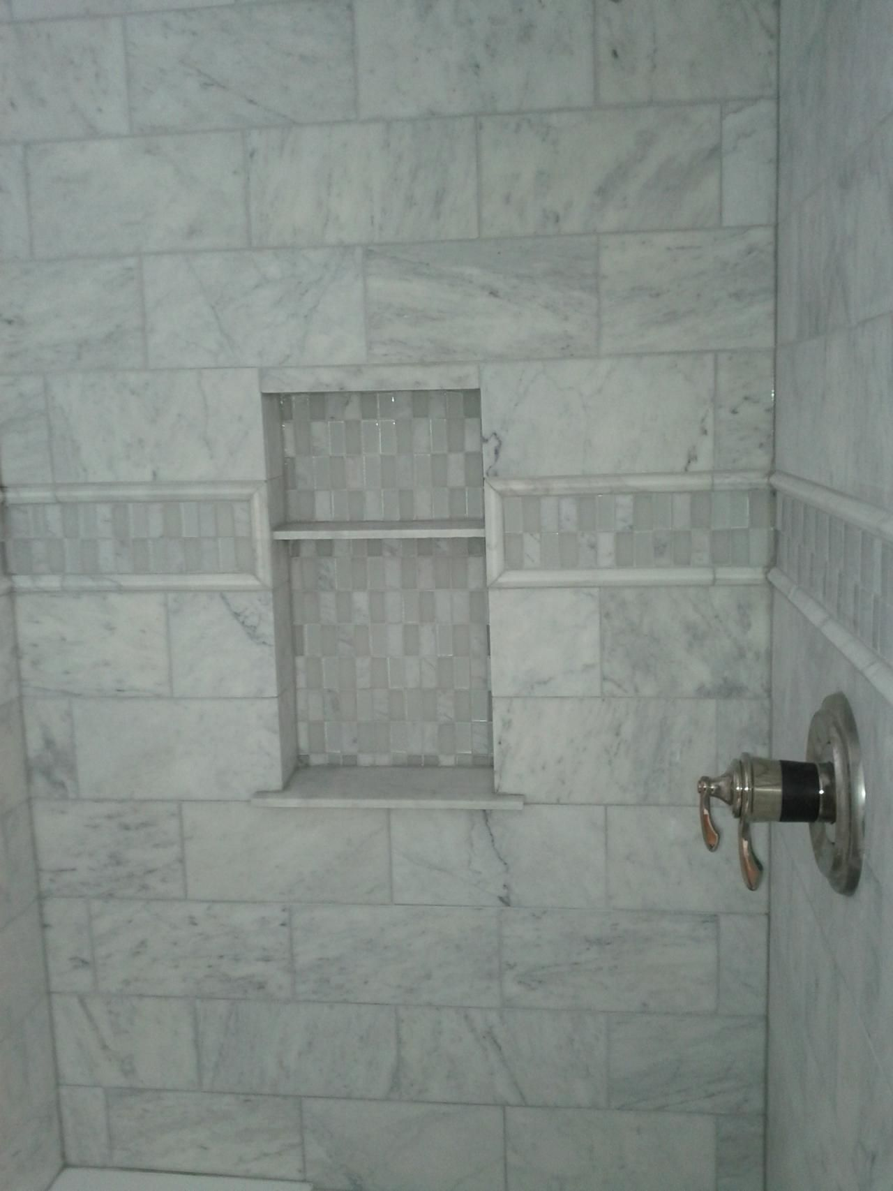 This Picture Shows A Marble Tile Shower With An Accent Strip And An Inset Shelf For The Home