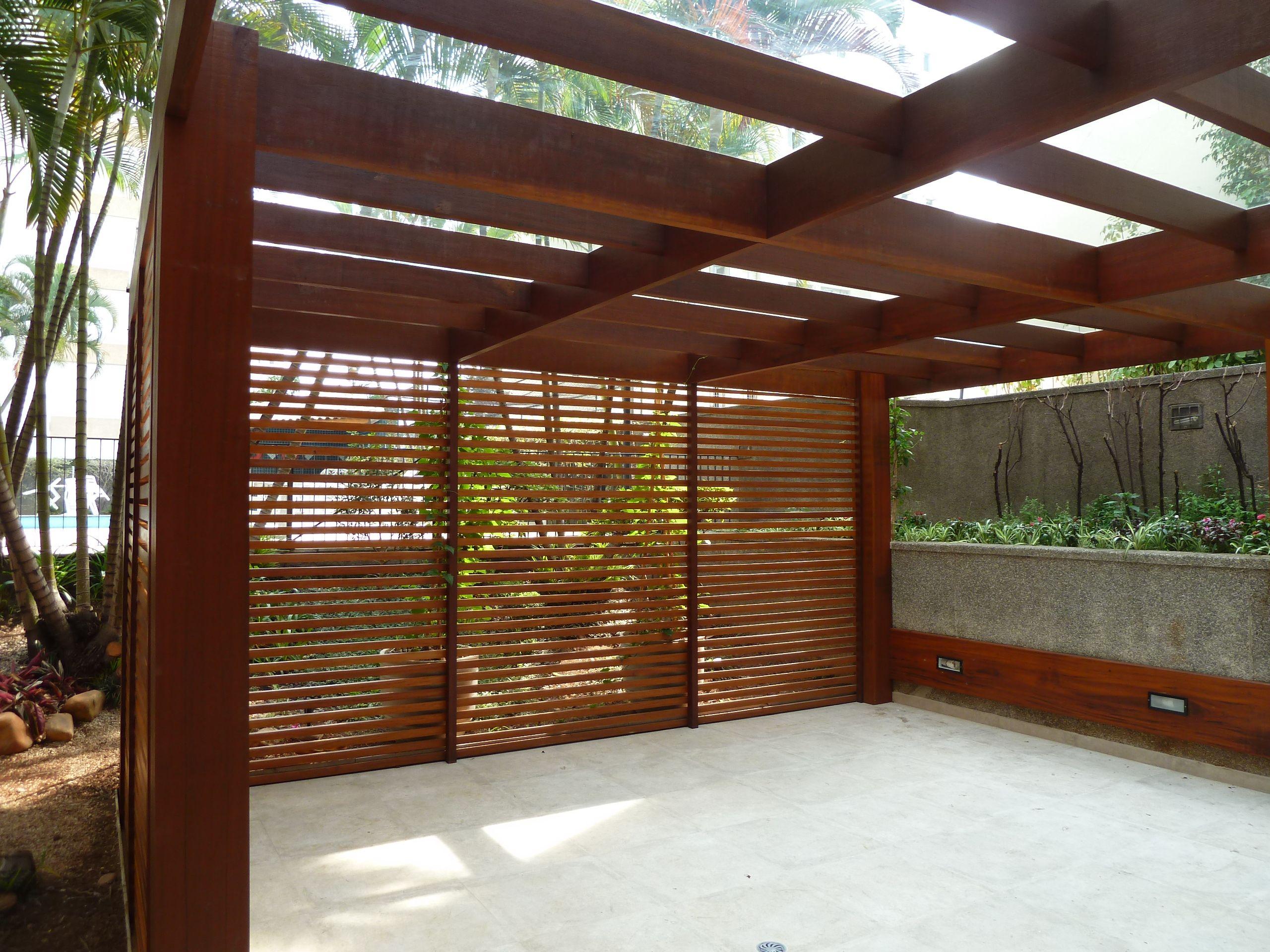 Projeto de Ana Donadio - Pergolado em madeira com cobertura de vidro para área da churrasqueira de um condominio