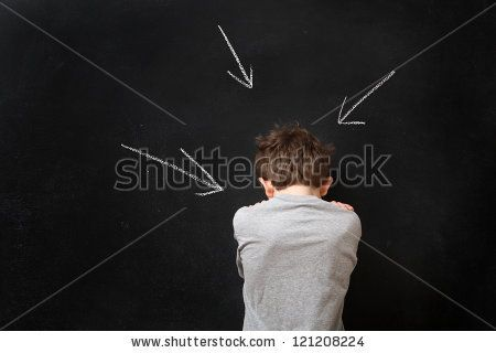 Sad boy standing at a blackboard with arrows by Suzanne Tucker, via Shutterstock