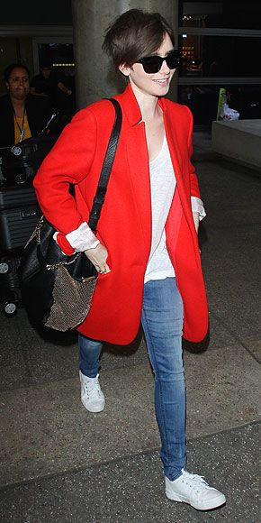 Love Her Outfit! Star Style to Steal | LILY COLLINS | Here's a much more practical airport outfit than Miranda's, which will look equally cute when worn to brunch or movie night. A simple jeans (hers are Ström Brand)-and-tee look like Lily's gets a major boost from two key pieces: Her classic red coat and her studded Jimmy Choo tote.