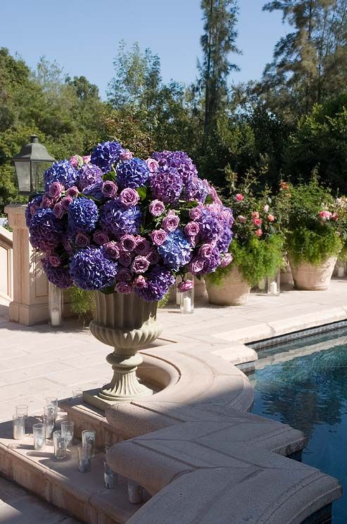 A large urn overflows with blue and purple hydrangeas