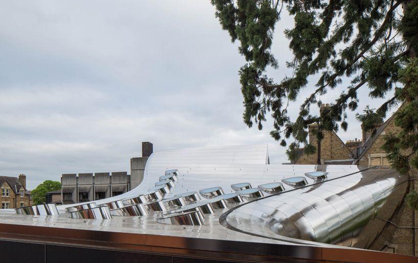 zaha hadid bridges oxford university campus with reflective library building