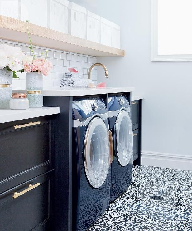 The Curated House White And Black Laundry Room Features A Long Floating Shelf Lined With Canvas Bins Suspended Over An Enclosed Washer Dryer
