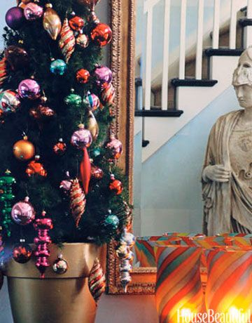 """""""After too many years of erecting a 20-foot behemoth, I've simplified. Now I get a pair of miniature trees, put them in gold-painted terra-cotta pots —  I spray them in my garage —  and place them on a console table flanking an antique mirror. I trim them with multicolored ornaments. No lights. No muss, no fuss. Easy to put up, easy to take down. You can't beat that."""" — JAMIE DRAKE   - HouseBeautiful.com"""