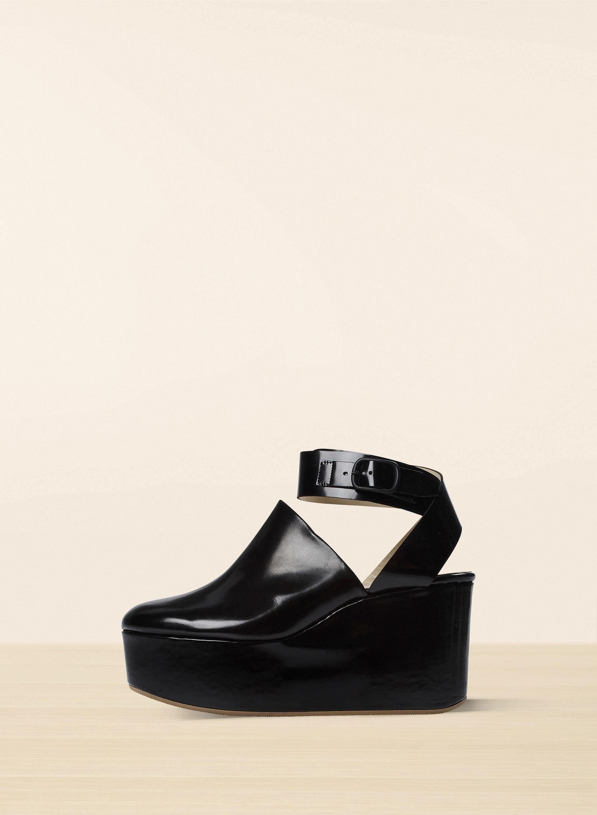 Kiiltonahkaisissa kengissä on kiilakorko ja korokepohja, suljettu varvasosa ja soljellinen nilkkahihna. Valmistettu Italiassa.