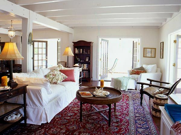 living room, white slipcovered sofa, oriental rug, wood bookcase