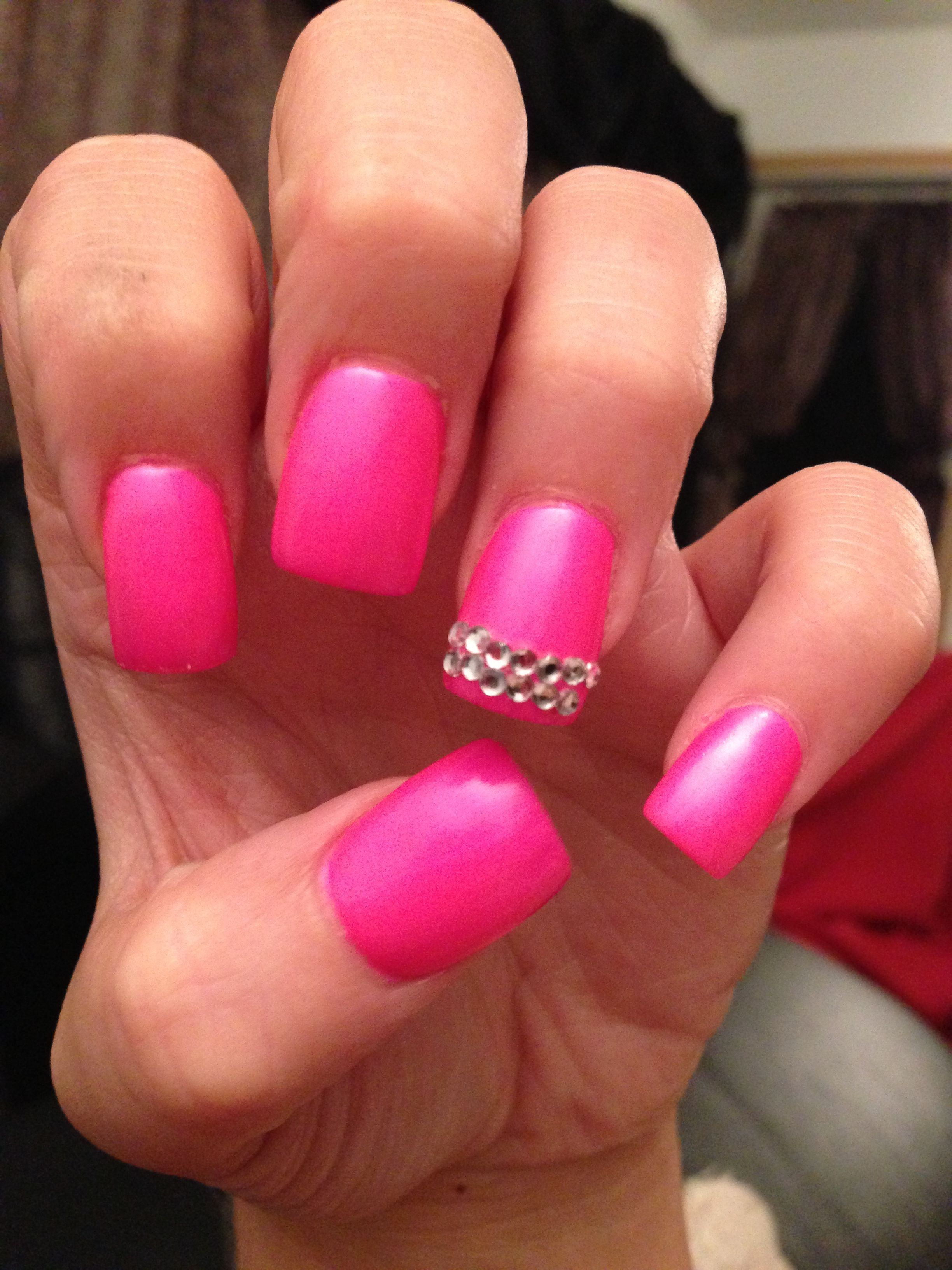 neon bright pink nails with rhinestones