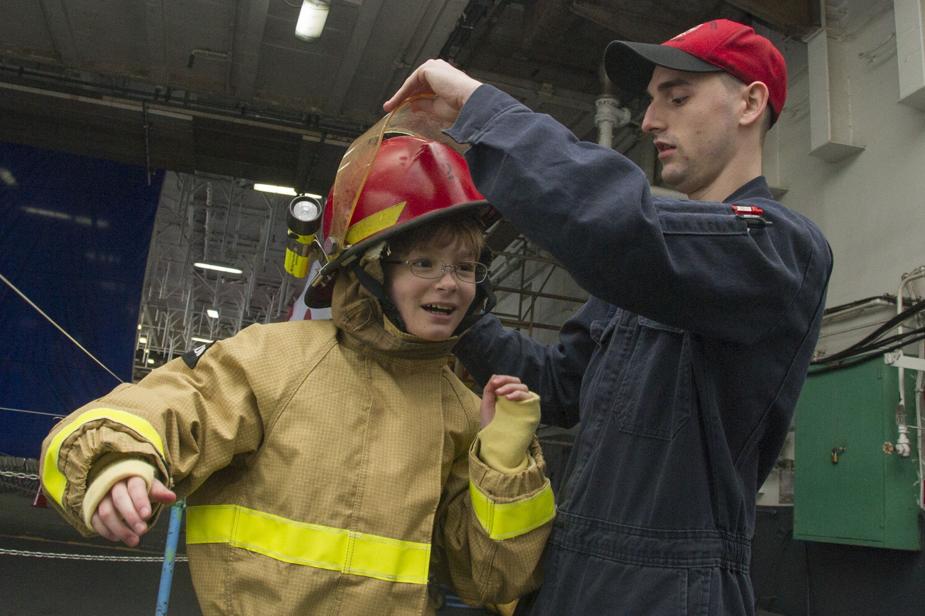 YOKOSUKA, Japan (April 2, 2015) Damage Controlman 2nd Class William Burkett, from Croydon, Pa., helps a 6th grade student at Yokosuka Middle School don firefighting gear during the annual Science Technology, Engineering and Math (STEM) conference aboard the Nimitz-class aircraft carrier USS George Washington (CVN 73). George Washington and its embarked air wing, Carrier Air Wing (CVW) 5, provide a combat-ready force that protects and defends the collective maritime interests of the U.S. and…