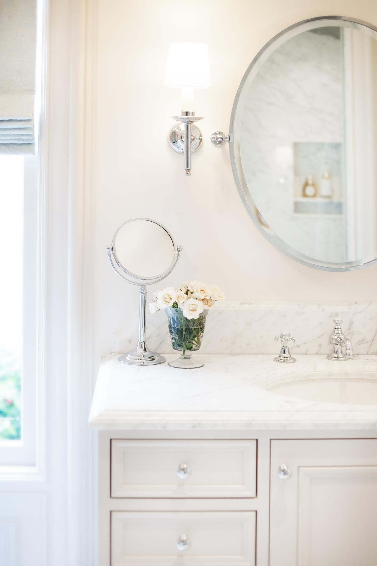 An elegant traditional vanity s a luxurious finish with a white marble countertop A large oval mirror and stainless sconce plete the space