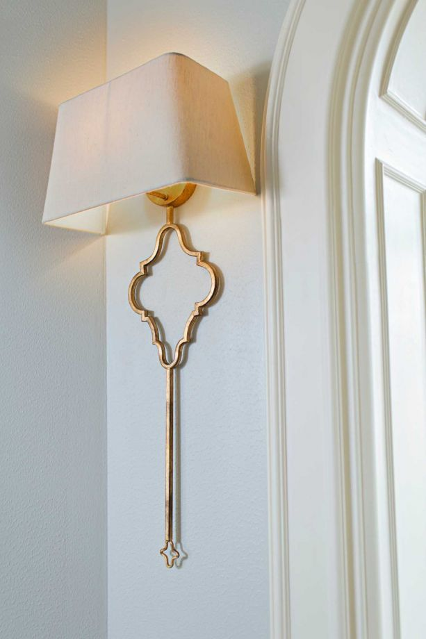 Fresh paint and a lighter sconce brighten up the Lilja's entryway, which divides the two redesigned rooms.