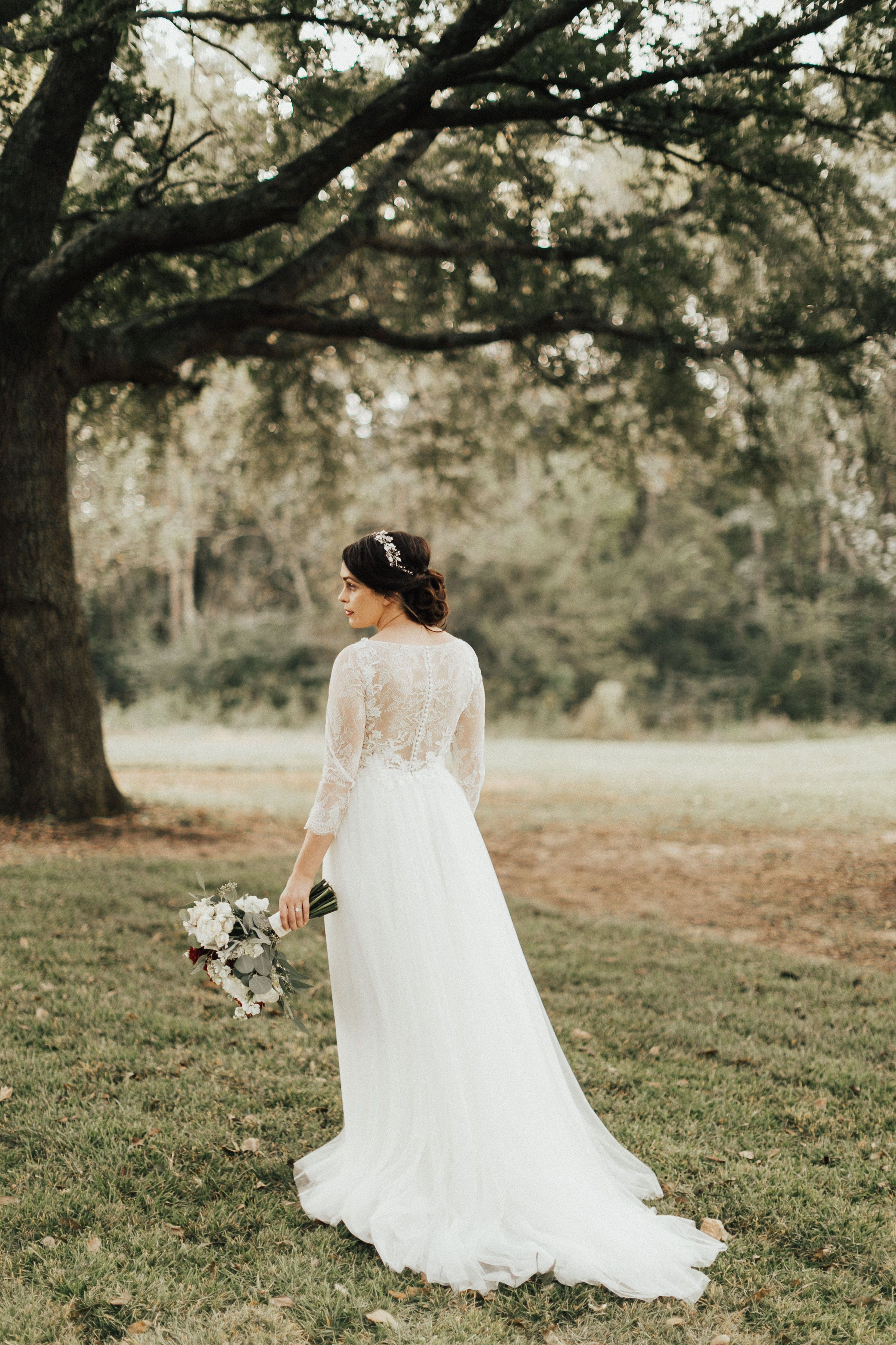A bride standing on her familyus farm in a lace back dress from