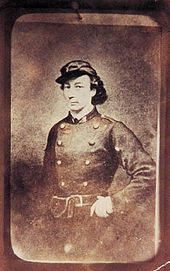 Louise Michel, née le 29 mai 1830 à Vroncourt-la-Côte, Haute-Marne et morte le 9 janvier 1905 à Marseille, alias « Enjolras », est une institutrice, militante anarchiste, franc-maçonne, aux idées féministes et l'une des figures majeures de la Commune de Paris. Première à arborer le drapeau noir, elle popularise celui-ci au sein du mouvement libertaire. WIKIPEDIA Louise Michel en tenue de fédéré