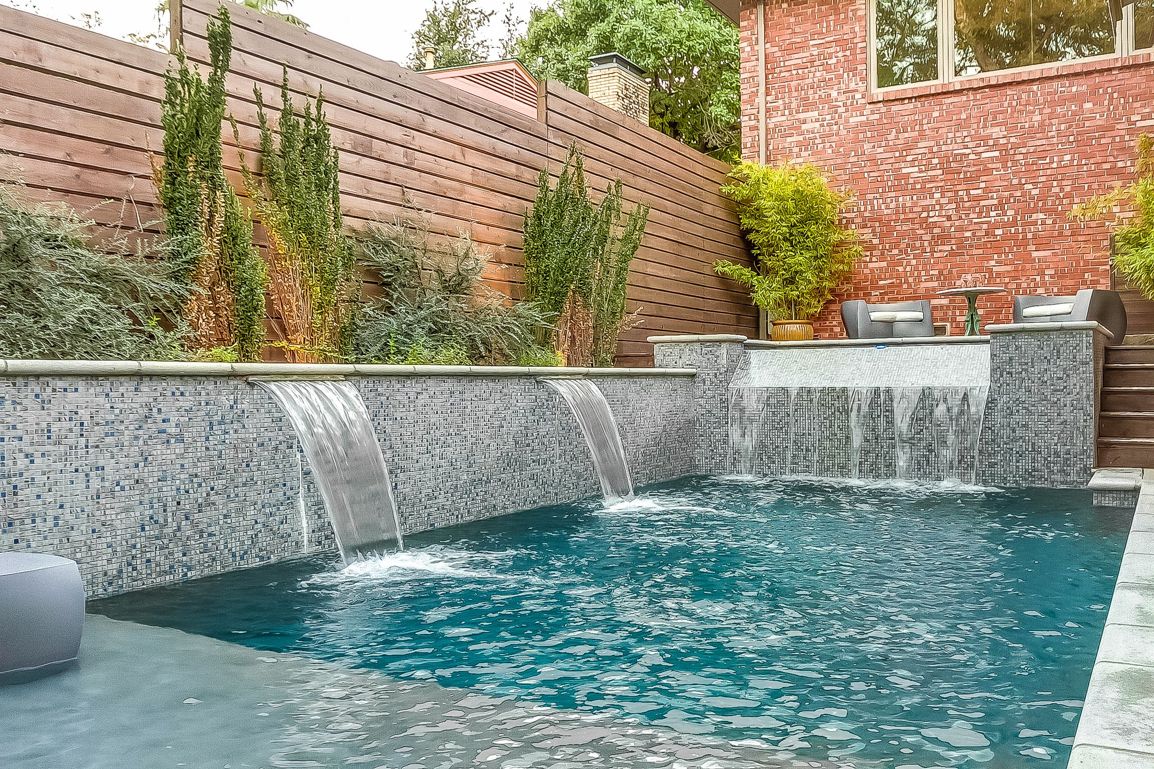 Raised Wall With Custom Glass Tile Two Foot Sheer Descents And Spa With Infinite Edge Spillway