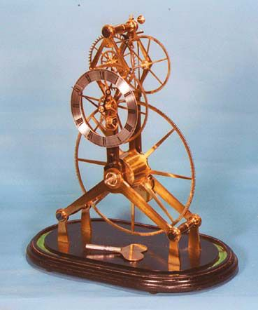 "John Wilding - A ""LARGE WHEEL"" SKELETON CLOCK—This clock features simplicity of design in the inverted ""Y"" frames together with the large main wheel. A further interesting note is the equal size of both the third and escape wheels. This balances the upper part of the clock. It is driven by a mainspring in a ""gong"" barrel and has optional stopwork."