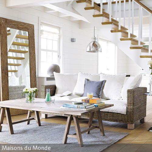 Der offene Wohnraum mit der SItzecke, die unter der Treppe liegt, ist im rustikalen Stil mit viel Holz und einem Rattansofa eingerichtet. Die groben Dielen in…