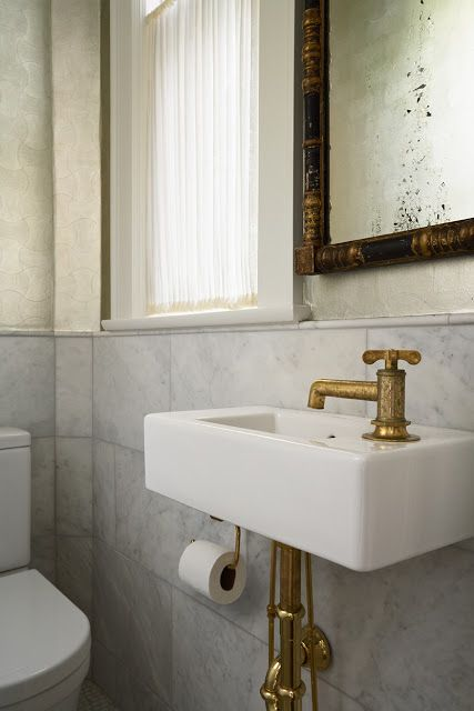 Gold faucet and wall hung sink in powder room made out of - Powder room sink ideas ...