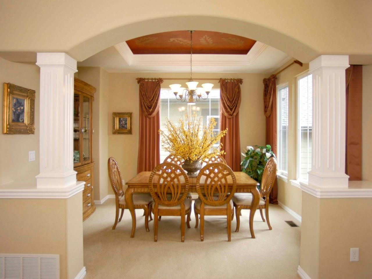 Elegant draperies, columns and an arched soffit help define this dining area as a formal space to entertain guests. The space's tray ceiling is painted a dark shade of salmon to match the dramatic window treatments.