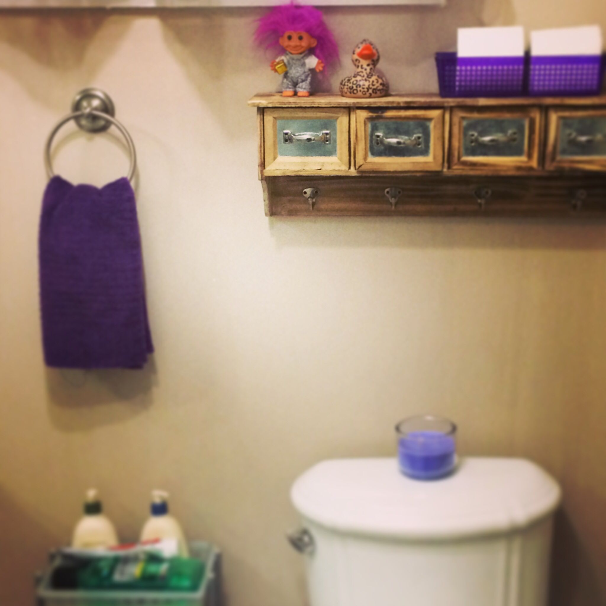 Purple accents brighten the drab paint job in the bathroom. #smallspace #interiordesign