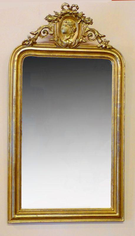 Antiguo espejo Frances con copete elaborado con guirnaldas y flores, como también talla de retrato clasico, todo dorado sobre escayola de Paris, en talla de madera.