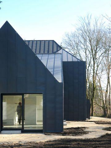 Une maison noire s\'immisce entre les arbres et la rivière ...