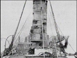 Antofagasta ... Poco después de haber sido remolcado a Mejillones, el monitor Peruano Huáscar, aún humeante es inspeccionado por personal de la Maestranza del Ferrocarril para reparar sus daños, efecto del certero fuego del blindado Cochrane.