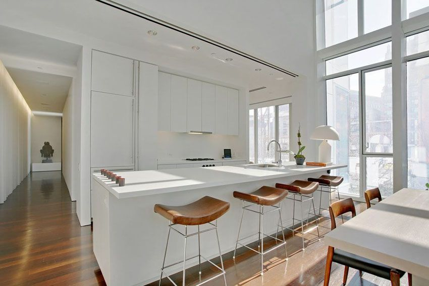 modern white kitchen with quartz counters flat panel cabinets and open dining area