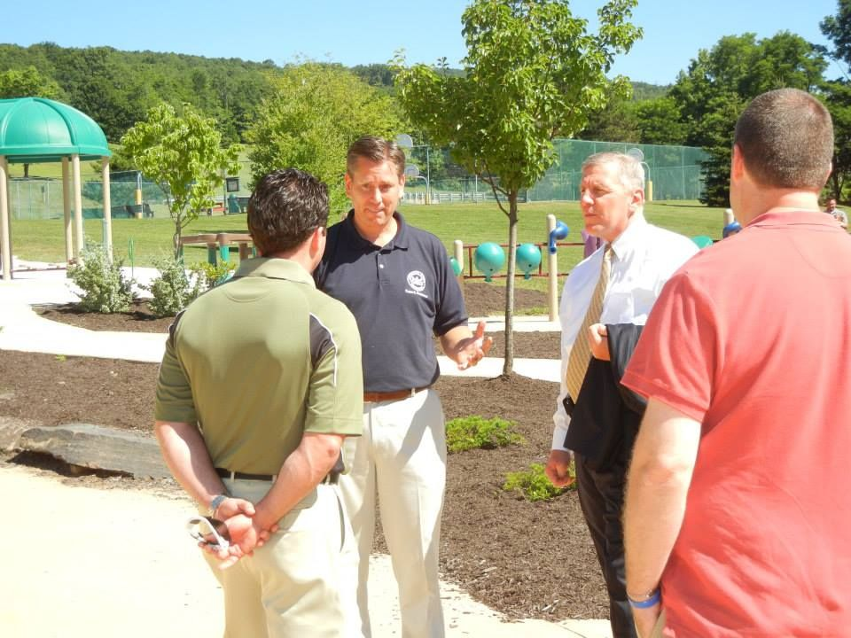 Bill Davis, Lackawanna County Parks and Recreation Director, gives assembled officials a tour of the boundless playground at McDade Park.