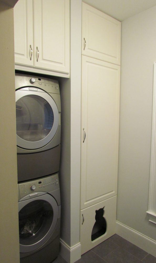 Photo of Stacked washer dryer next to tall pantry cabinet with custom cat shaped door to …