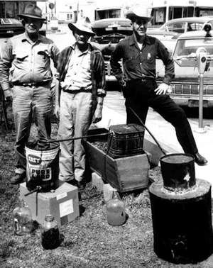 Moonshiners continued operating in Baxter County during the 1960s. This April 15, 1965, photo shows (from left) Federal Revenue Officer Robert Taylor of Fort Smith, Richard 'Dick' Pinkston and Sheriff Emmett Edmonds with a confiscated still.